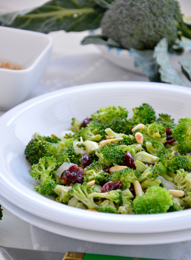 Broccoli Apple Salad with almonds and turmeric in a white bowl ready to eat