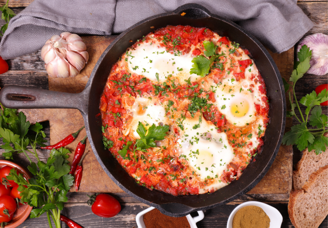 shakshuka in a cast iron pan with ingredients around on a rustic background